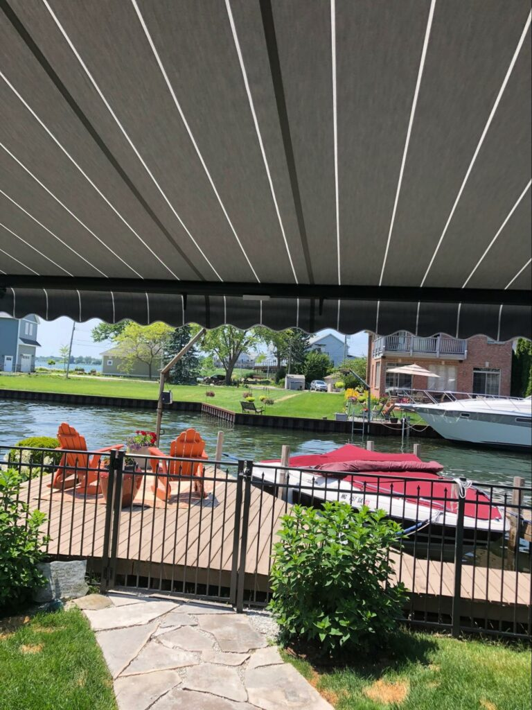 home along the water featuring rolling striped awning for their lanai miami, florida retractable deck roof   sun protection